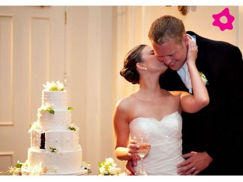 novios besandose junto al pastel